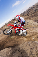 Motorcyclist riding dirt bike on hillside