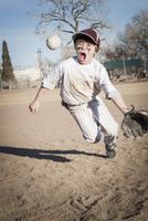 Caucasian boy catching baseball on field 11018067197| 写真素材・ストックフォト・画像・イラスト素材|アマナイメージズ