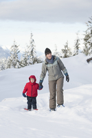 Caucasian mother and son walking in snow