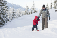 Caucasian mother and son snowshoeing on hillside