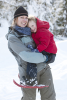 Caucasian mother and son snowshoeing
