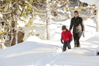 Caucasian mother and son snowshoeing on path