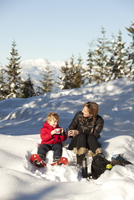Caucasian mother and son drinking hot cocoa in snow