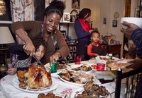 Mother and daughter carving turkey at holiday dinner