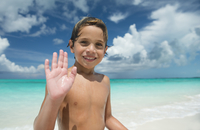 Hispanic boy waving on beach
