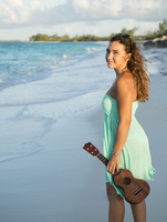 Hispanic teenage girl holding ukulele on beach