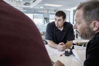 Businessmen talking in office meeting