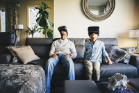 Mixed race father and daughter using virtual reality goggles 11018067469| 写真素材・ストックフォト・画像・イラスト素材|アマナイメージズ