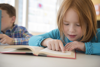 Caucasian student reading in classroom