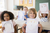 Students showing drawings in classroom