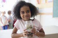 Student holding savings jar in classroom
