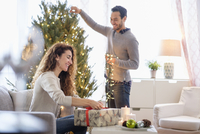 Couple decorating for Christmas in living room