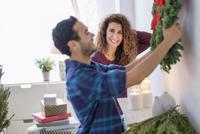 Couple hanging Christmas wreath
