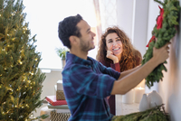 Couple hanging Christmas wreath