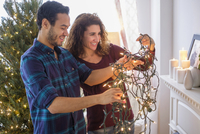 Couple untangling Christmas lights