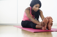Mixed race woman stretching on yoga mat