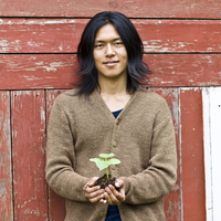 Japanese man holding potted plant outdoors