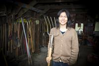 Japanese gardener holding pitchfork in barn