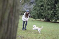 Japanese woman playing with dog in park