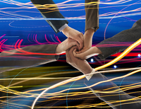 Business people holding hands in light trails