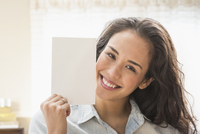 Mixed race woman holding blank card