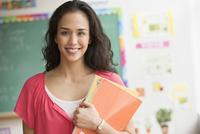 Mixed race teacher holding books in classroom