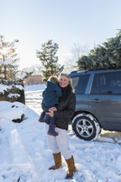 Caucasian mother holding son in snow