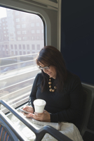 Hispanic woman using cell phone on train