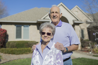 Older Caucasian couple smiling in yard