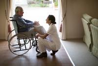 Nurse talking to patient in wheelchair 11018068296| 写真素材・ストックフォト・画像・イラスト素材|アマナイメージズ