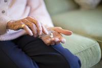 Older Caucasian woman holding medication