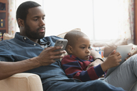 Father and son using technology on sofa