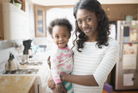 Black mother holding daughter in kitchen