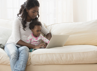 Black mother and daughter using laptop on sofa