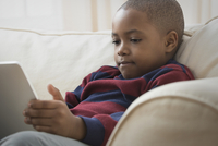 Mixed race boy using digital tablet on sofa