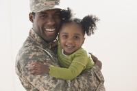 Returning soldier hugging daughter