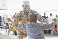 Returning soldier hugging son