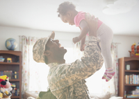 Soldier lifting daughter indoors