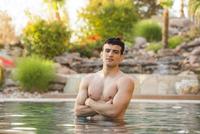 Hispanic man standing in swimming pool