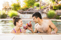 Couple toasting with cocktails in swimming pool