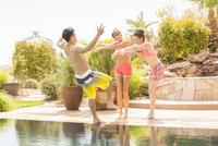 Women pushing man into swimming pool