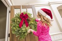 Caucasian girl hanging Christmas wreath 11018068555| 写真素材・ストックフォト・画像・イラスト素材|アマナイメージズ