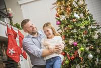 Caucasian father and daughter hugging near Christmas tree 11018068559| 写真素材・ストックフォト・画像・イラスト素材|アマナイメージズ