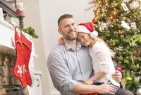 Caucasian father and daughter hugging near Christmas tree 11018068560| 写真素材・ストックフォト・画像・イラスト素材|アマナイメージズ
