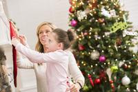 Caucasian mother and daughter hanging Christmas stockings 11018068561| 写真素材・ストックフォト・画像・イラスト素材|アマナイメージズ