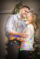 Caucasian couple wrapped in Christmas lights 11018068563| 写真素材・ストックフォト・画像・イラスト素材|アマナイメージズ