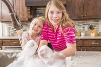Caucasian girls washing hands in kitchen sink