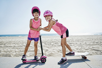Girls playing on skateboard at scooter at beach