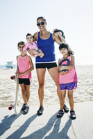Mother and daughters holding kettle bells at beach