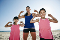 Mother and daughters flexing muscles at beach